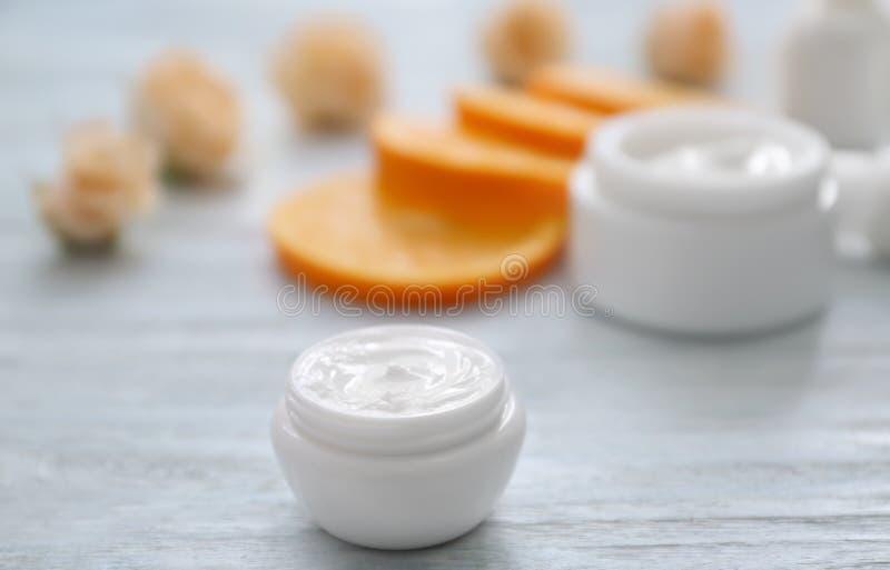 Crème avec l'extrait de fines herbes sur la table en bois blanche images stock