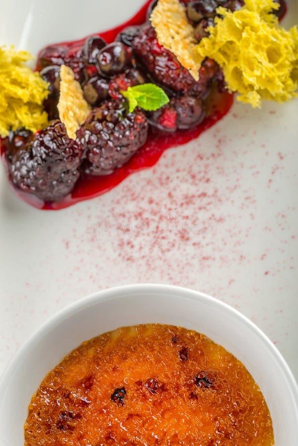Crème brulée avec le fruit chaud de forêt servi du plat blanc dans le restaurant moderne, photographie de produit pour la gastron photographie stock libre de droits