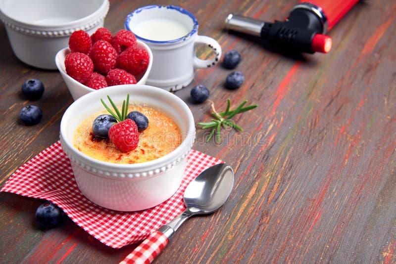Crème-brulée con il lampone, il mirtillo ed i rosmarini con il ingredi fotografia stock