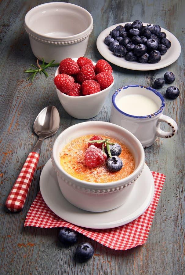 Crème-brulée con le bacche e gli ingredienti su legno rustico immagini stock libere da diritti
