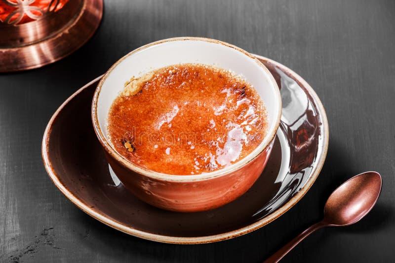 Crème-brulée o dessert alla panna francese della vaniglia con zucchero caramellato con tè su fondo scuro fotografie stock