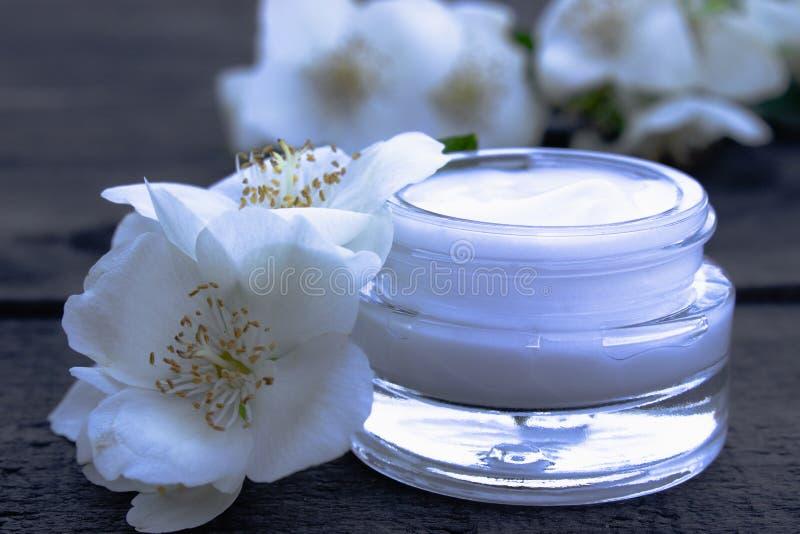 Crème cosmétique dans un pot en verre avec des fleurs de jasmin sur un fond en bois images libres de droits