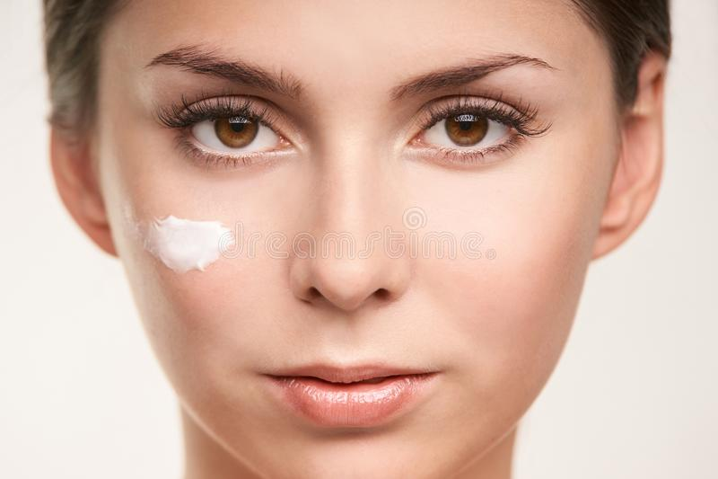 Crème cosmétique de facteur de SPF sur le visage Beau visage de fille de soin UV image stock