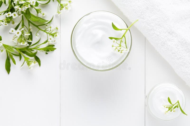 Crème cosmétique de visage de fines herbes avec le produit hygiénique de soins de la peau de fleurs image stock