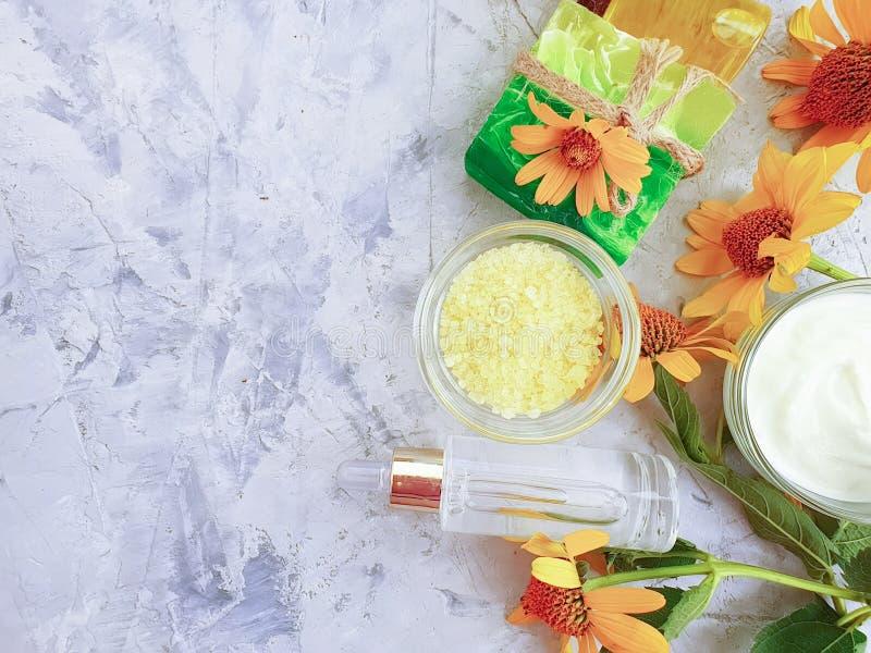 Crème cosmétique, huile, fleurs jaunes faites maison de pureté naturelle de sel sur un fond concret photos stock