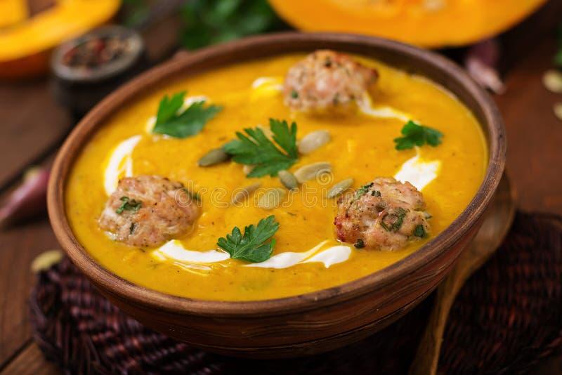 Crème délicieuse de soupe à potiron avec des boulettes de viande faites de viande hachée de dinde dans une cuvette sur une table  images libres de droits