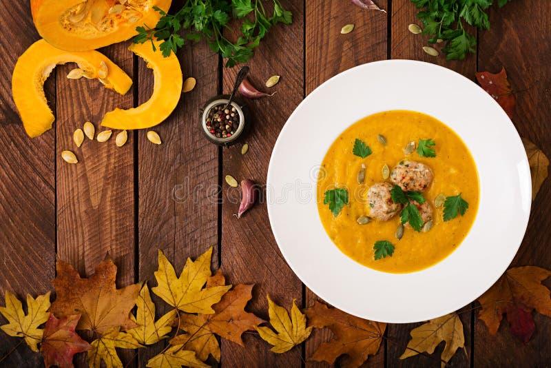 Crème délicieuse de soupe à potiron avec des boulettes de viande faites de viande hachée de dinde dans une cuvette sur une table  photo libre de droits