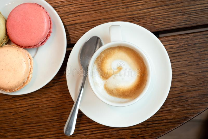 Crème d'expresso dans la tasse en céramique blanche avec la soucoupe et spon à côté d'un plat avec des macarons sur la surface en image libre de droits