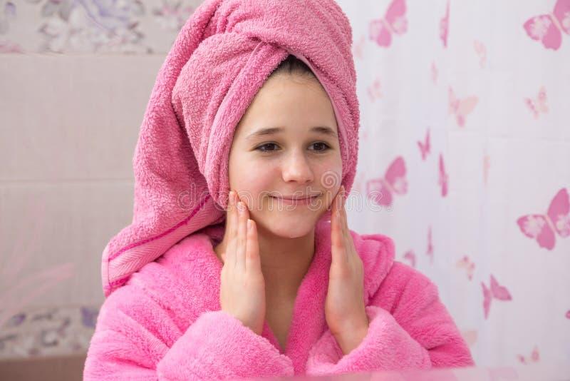 Crème de cosmétiques d'utilisation de jeune fille pour son visage dans la salle de bains images libres de droits