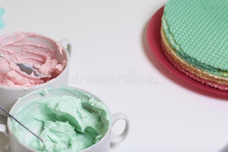 Crème de différentes couleurs pour décorer le gâteau de gaufre Gâteaux ronds de gaufrette de différentes couleurs Pour faire le g image libre de droits