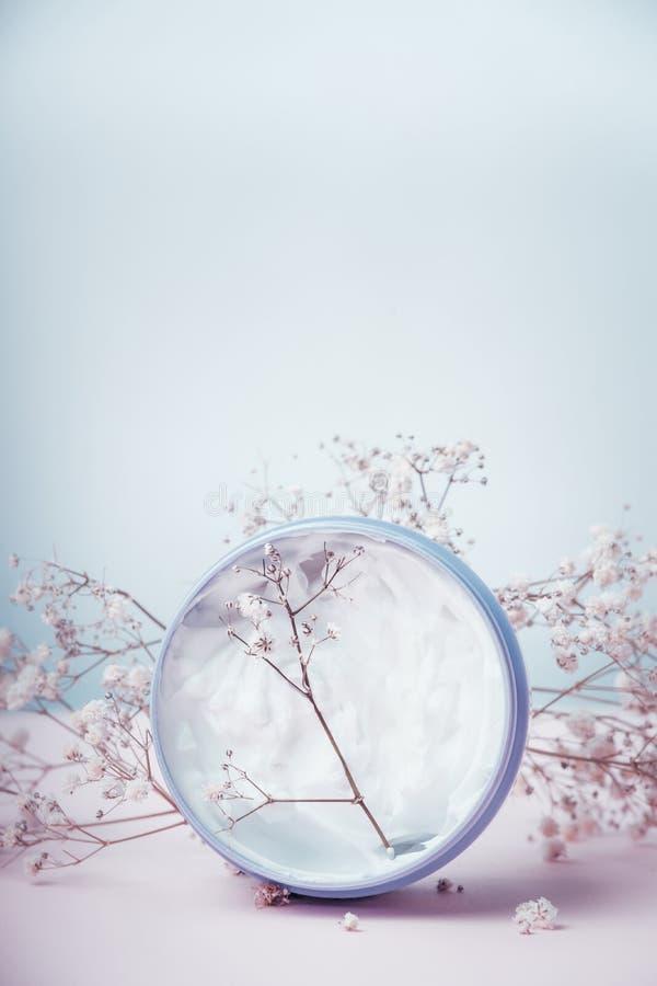 Crème de fines herbes dans le pot avec des fleurs dans la couleur en pastel images libres de droits