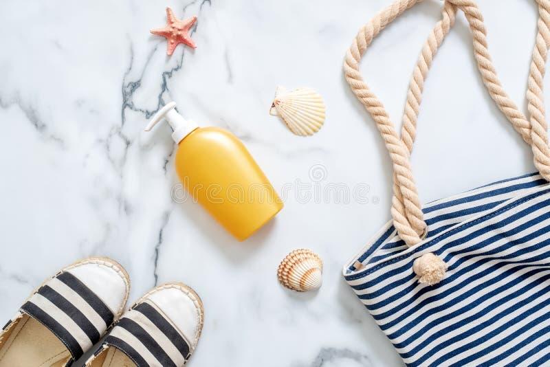 Crème de protection solaire dans une bouteille jaune, des sandales rayées et un sac de plage, coquillages sur le fond de marbre P photo libre de droits
