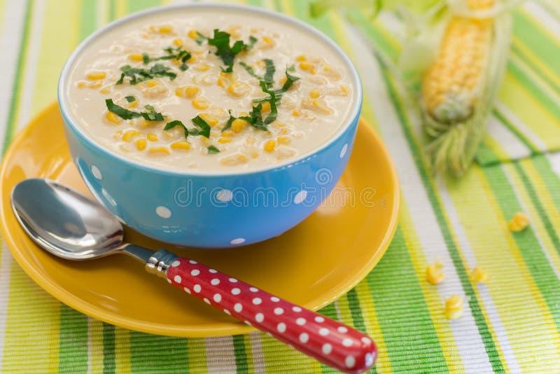 Crème de soupe à maïs dans la cuvette bleue avec l'épi frais du maïs image libre de droits