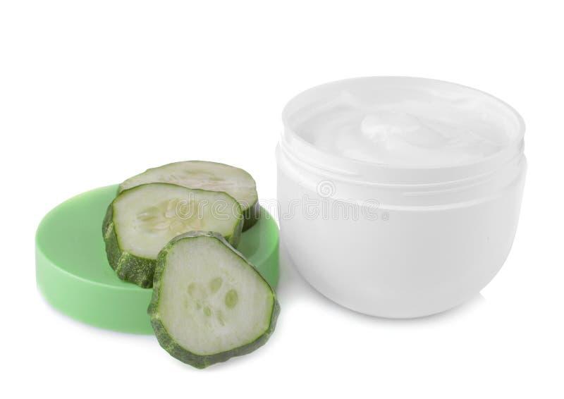 Crème de visage avec l'extrait de concombre avec des concombres sur un fond blanc D'isolement photographie stock