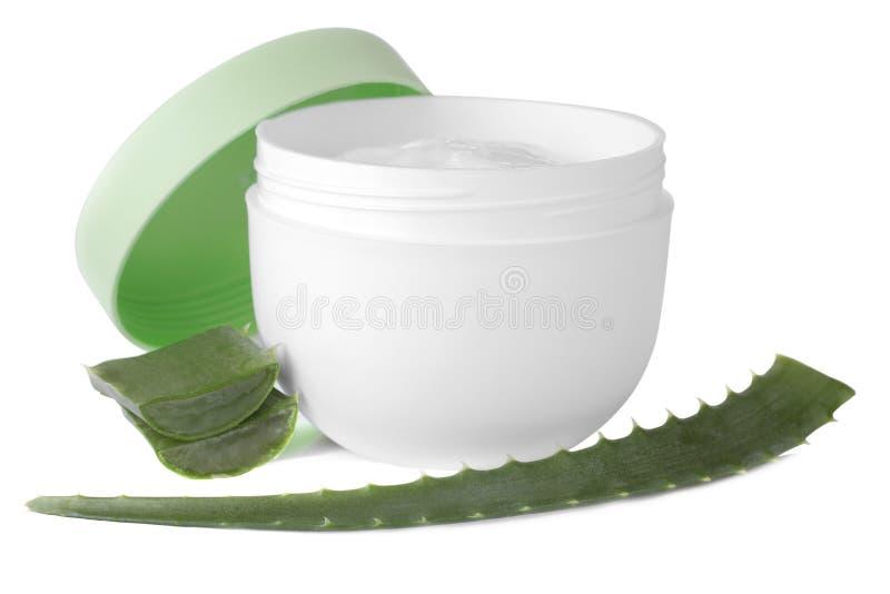 Crème de visage dans un pot avec le couvercle vert avec l'extrait d'aloès et l'aloès frais à côté d'un fond blanc D'isolement photo libre de droits