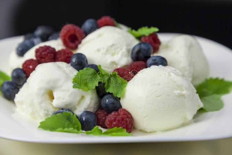 crème glacée avec des framboises, des myrtilles et des feuilles en bon état photo libre de droits