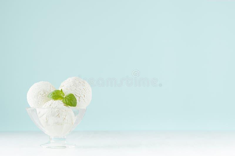Crème glacée crémeuse douce dans le bol en verre transparent élégant avec la menthe verte sur la table en bois blanche et le mur  photo libre de droits