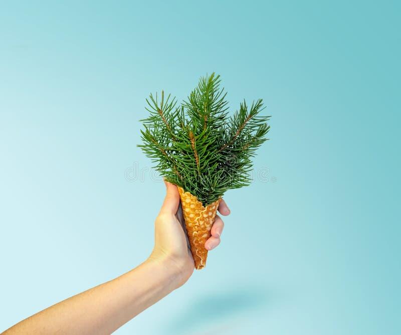 Crème glacée d'arbre de Noël chez la main de la femme sur le fond bleu de Ligth Concept d'an neuf Composition minimale en vacance photographie stock