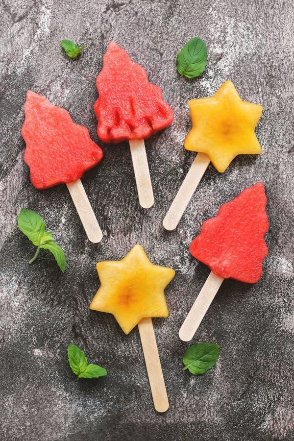 Crème glacée de pastèque et de pêche sous forme d'arbre de Noël et étoile Dessert de fruit d'été sur un bâton Dessert de Noël image libre de droits
