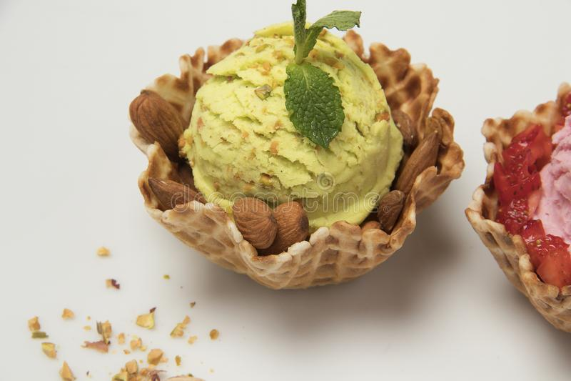 Crème glacée de pistache à l'arrière-plan blanc de panier de cornet de biscuit photos libres de droits