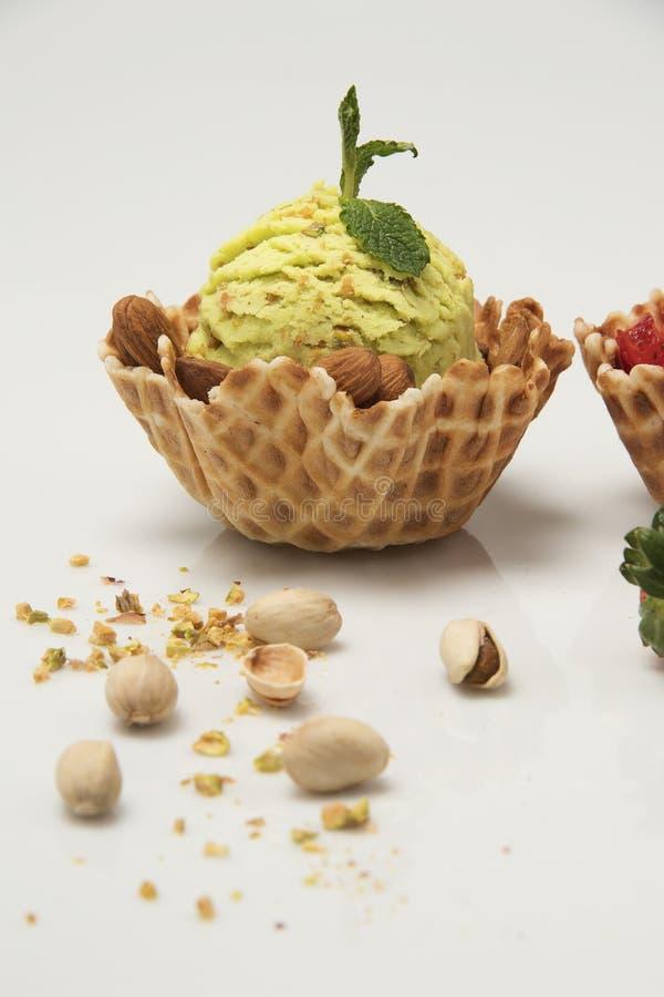 Crème glacée de pistache à l'arrière-plan blanc de panier de cornet de biscuit photographie stock libre de droits