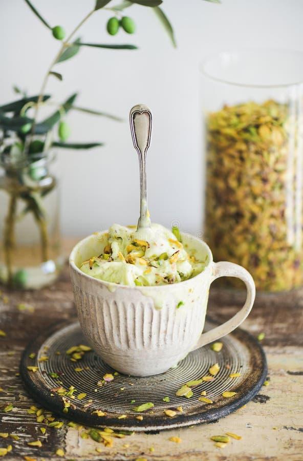 Crème glacée de pistache dans la tasse avec des pistaches images libres de droits