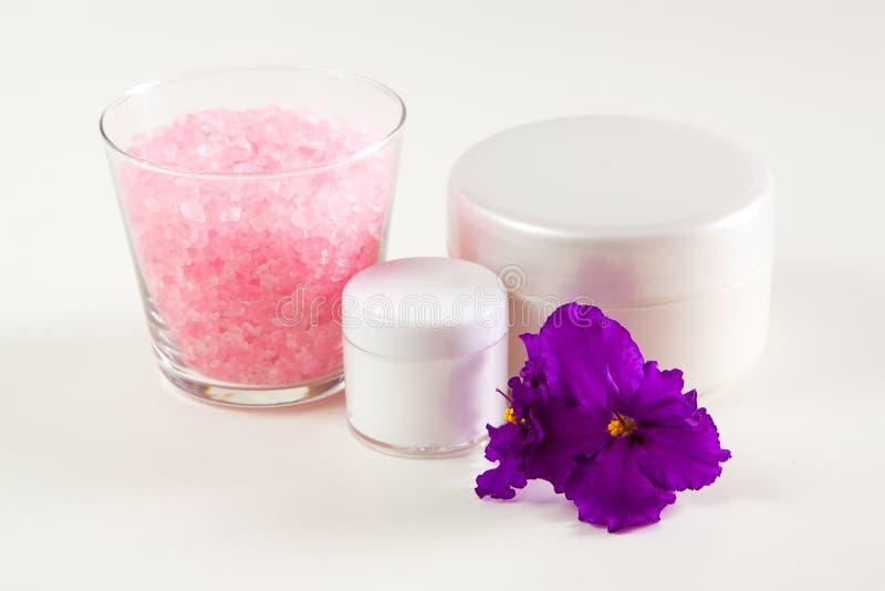 Crème hydratante, sel de mer et violette sur un fond blanc images libres de droits