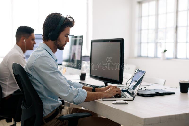 Créateurs d'application travaillant sur des ordinateurs dans le bureau photos stock