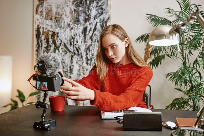 Création du contenu Portrait de blogger féminin installant son appareil photo numérique monté par trépied avant de faire une nouv photos stock