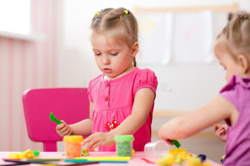 Créativité d'enfants Les enfants sculpte de l'argile La petite fille mignonne moule de la pâte à modeler sur la table dans la crè image stock