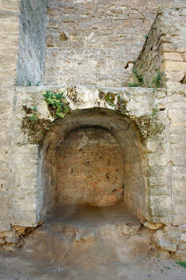 Créneau en pierre arqué enfoncé dans les murs en pierre image libre de droits
