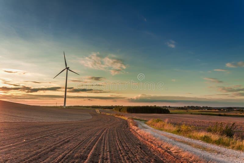 Crépuscule étonnant au champ avec la turbine de vent en automne images stock