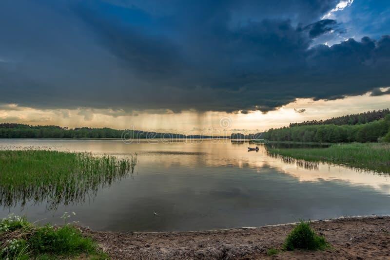 Crépuscule étonnant au lac d'été avec les nuages dynamiques image stock