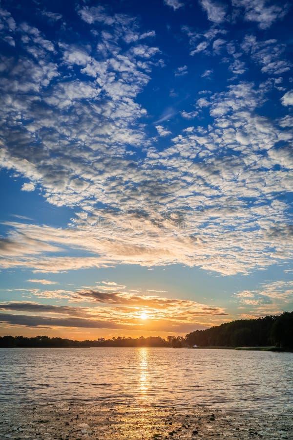 Crépuscule étonnant au lac d'été avec les nuages dynamiques photographie stock