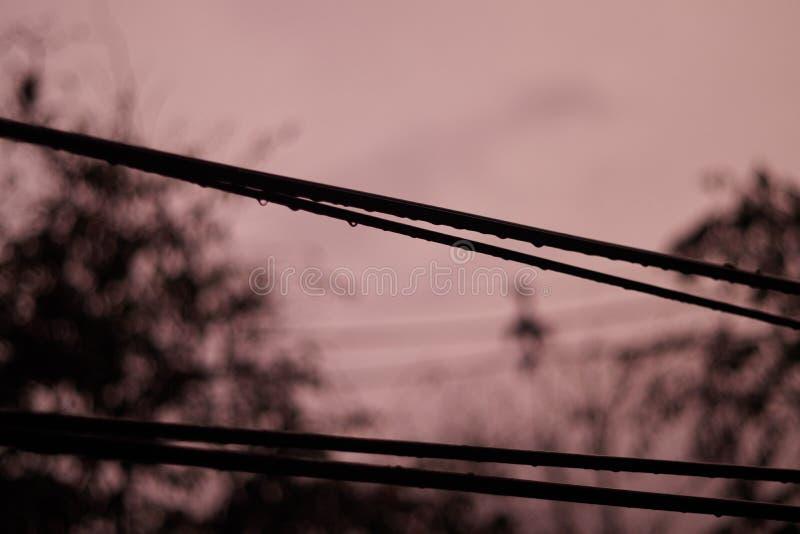 Crépuscule foncé de carmin avec la pluie et le câble images libres de droits