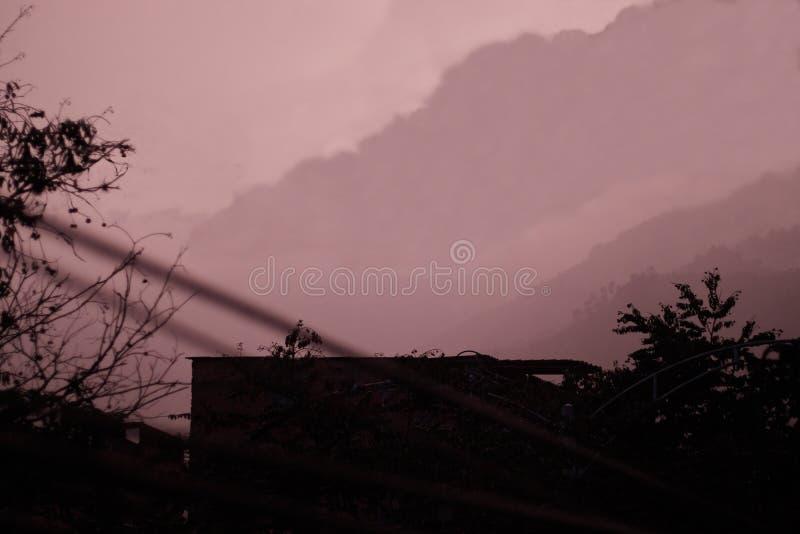 Crépuscule foncé de carmin avec la pluie et la montagne confinée photos libres de droits