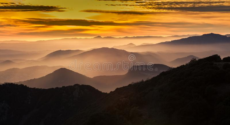 Crépuscule, vallées brumeuses et gammes de montagne photographie stock