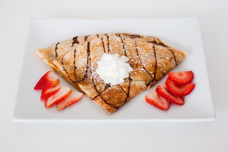 Crêpe avec les fraises fraîches arrosées avec du sucre images libres de droits