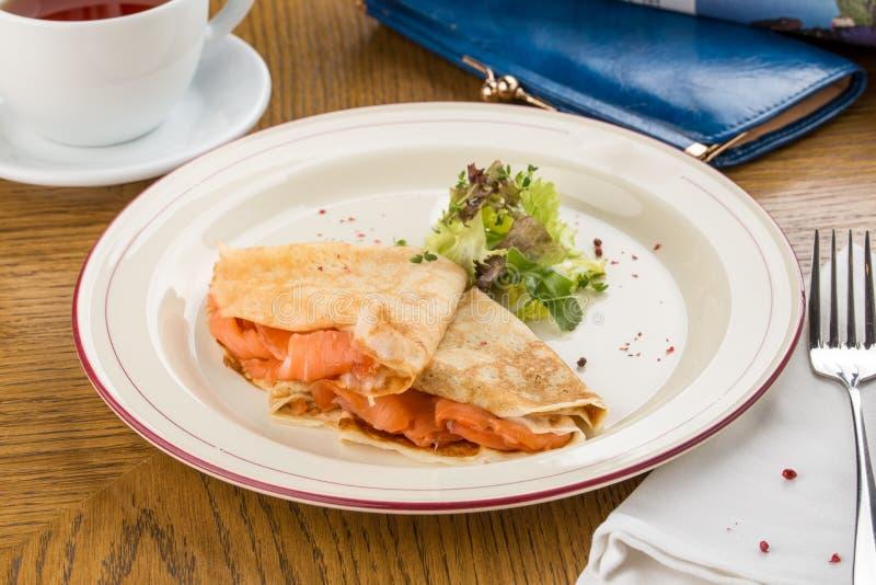 Crêpe con il salmone affumicato su un piatto bianco per la prima colazione sulla tavola di legno fotografie stock