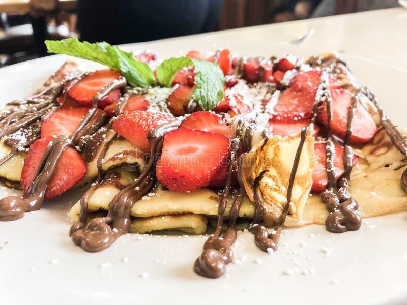 Crêpe con le fragole ed il cioccolato fuso Piegato, chiuda su immagine stock