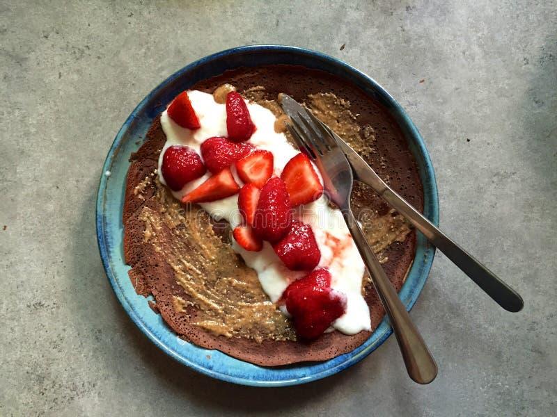 Crêpe de chocolat de plat avec du beurre d'écrou, crème, fraises fraîches image stock