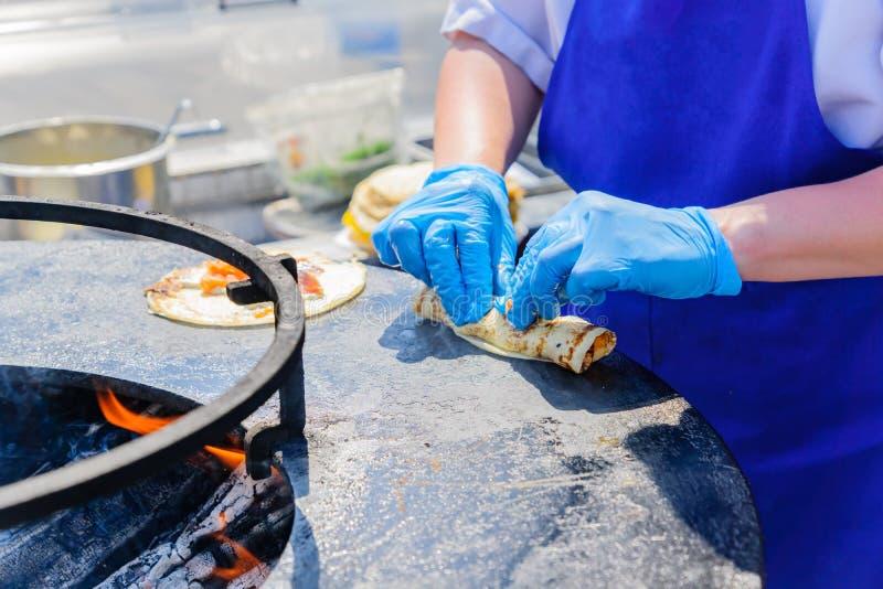 Crêpe de cuisinier de chef avec des saumons au festival Nourriture de rue préparée sur le gril images libres de droits