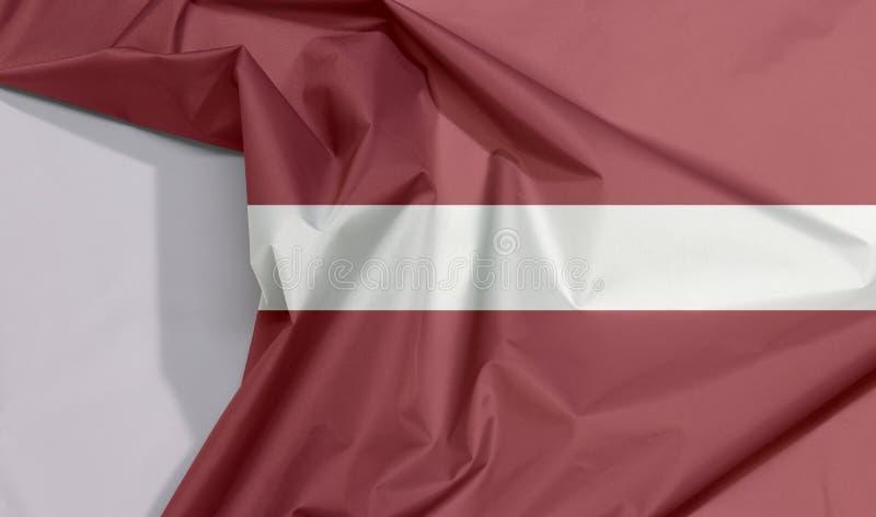 Crêpe et pli de drapeau de tissu de la Lettonie avec l'espace blanc photographie stock