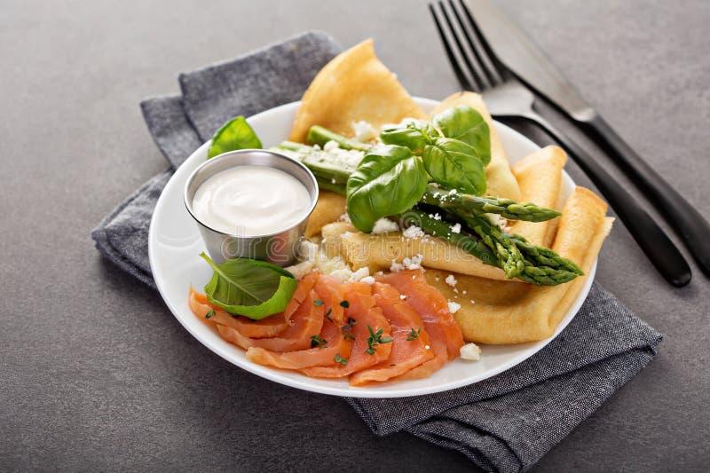 Crêpe saporiti con il salmone, la panna acida e l'asparago fotografia stock