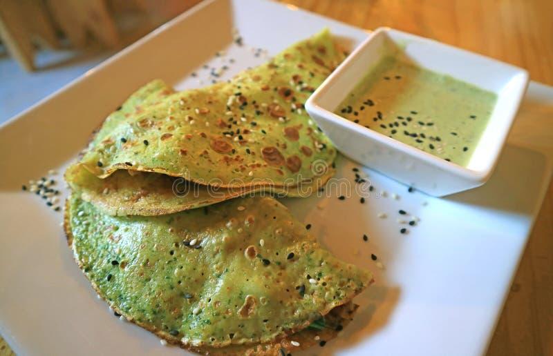 Crêpe saporiti deliziosi degli spinaci con la salsa di senape verde sul piatto bianco fotografia stock