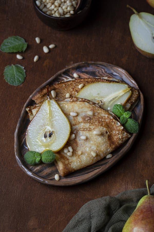 Crêpe sottili con la pera ed i pinoli del caramello fotografia stock