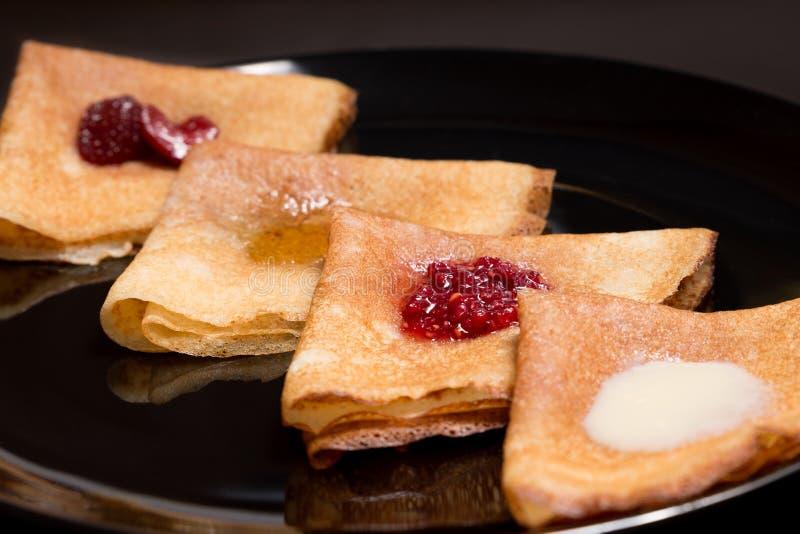 Crêpes avec de la confiture de fraise, la confiture de framboise, la crème sure et le miel images libres de droits