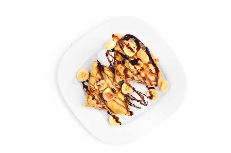 Crêpes avec la banane, la crème glacée et le habillage de chocolat - vue supérieure images stock