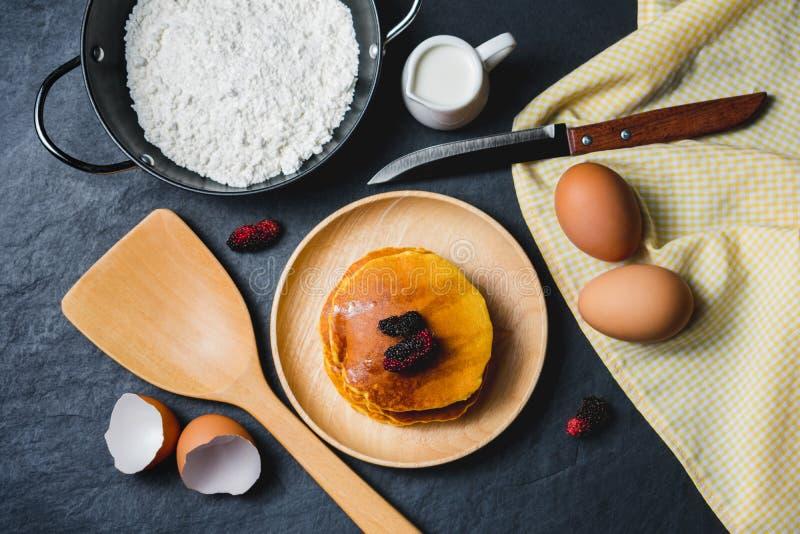 Crêpes avec la mûre et le miel frais sur le fond en pierre noir photographie stock libre de droits