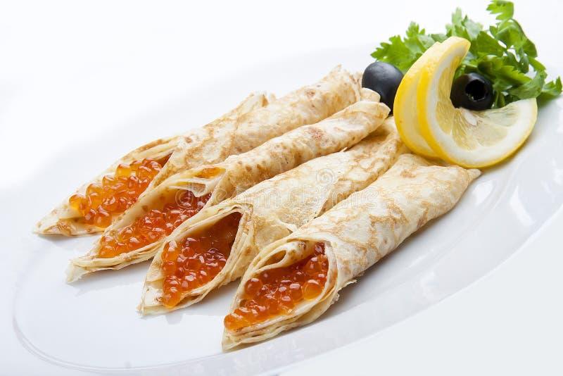 Crêpes avec le caviar rouge sur le fond blanc image stock